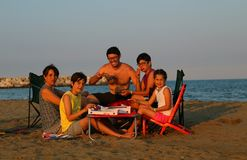 Happy family of five eats pizza on the beach Royalty Free Stock Image