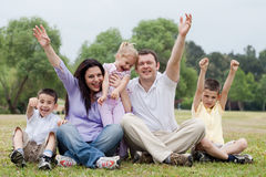 Happy family of five having fun by raising hands royalty free stock photography