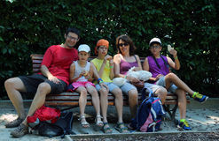 Happy family of five people eat sandwiches. On a bench during the sightseeing of the city stock image