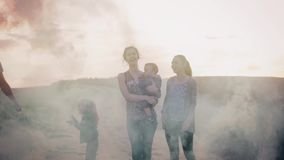 Happy family of five people spending time outdoors. Father holding a smoke grenade in nature and running with fume stock video