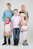 Happy family of five people. Youngest son looks up in the studio royalty free stock images