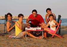 Happy family of five person  eats pizza on the beach Royalty Free Stock Image