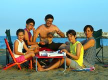 Happy family of five person eats pizza on the beach Royalty Free Stock Images