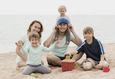 Happy family of five at sea shore. Happy family of five playing with sand on the beach at sea shore Stock Image