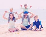 Happy family of five at sea shore Stock Photos