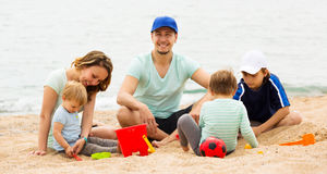 Happy family of five sitting at sandy beach Royalty Free Stock Image
