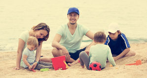 Happy family of five sitting at sandy beach. And resting royalty free stock photography