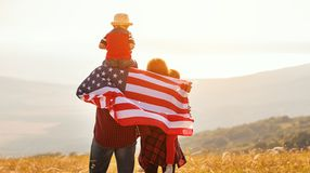 Happy family with flag of america USA at sunset outdoors royalty free stock images