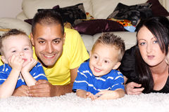 Happy family on floor. Happy family laying on floor and looking at the viewer Royalty Free Stock Photos