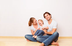 Happy family on  floor near  empty  wall in the apartment bought Royalty Free Stock Photography