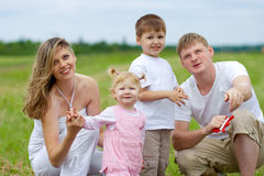Happy family fly a kite together in summer field. Happy family with pregnant wife fly a kite together in summer field Stock Photo
