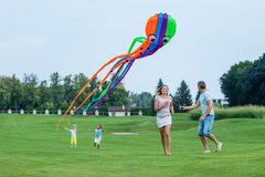 Happy family flying kite on a green field Royalty Free Stock Image