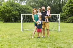 Happy family with football ball on a field Royalty Free Stock Photos