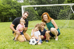Happy family with football ball on a field Stock Photography