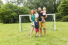 Happy family with football ball on a field Royalty Free Stock Photo