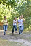 Portrait of happy family of four in autumn park running royalty free stock photography