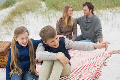 Happy family of four at a beach picnic Royalty Free Stock Image