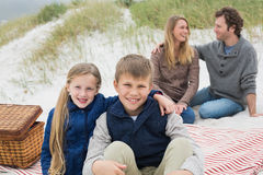 Happy family of four at a beach picnic Royalty Free Stock Photography