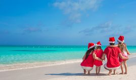 Happy family of four on beach in red Santa hats Royalty Free Stock Images