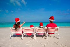Happy family of four on beach in red Santa hats Royalty Free Stock Photography
