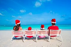 Happy family of four on beach in red Santa hats Stock Image