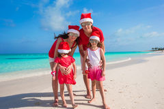 Happy family of four on beach in red Santa hats Royalty Free Stock Image