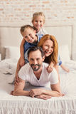 Happy family of four in bedroom Royalty Free Stock Photography