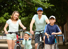 Happy family of four with bicycles and scooter. In vacation at park Stock Photography