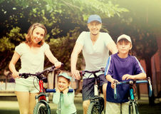 Happy family of four with bicycles and scooter. In vacation at park Stock Photo