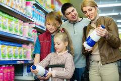 Happy family of four buying pasteurized milk Royalty Free Stock Photos