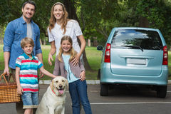Happy family of four with car at picnic Stock Photos