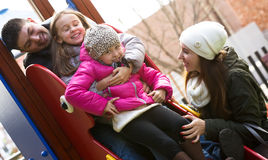 Happy family of four at children's playground Stock Photography