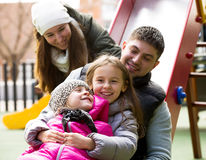 Happy family of four at children's playground Royalty Free Stock Photos