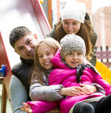 Happy family of four at children`s playground Royalty Free Stock Photos