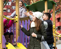 Happy family of four at children's playground Royalty Free Stock Image