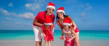 Happy family of four in Christmas Hats on white royalty free stock images