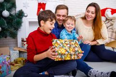 Happy family at Christmas in the house, on the background of a fireplace and a Christmas tree with a gift. Stock Images