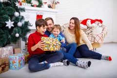 Happy family at Christmas in the house, on the background of a fireplace and a Christmas tree with a gift. Royalty Free Stock Photography