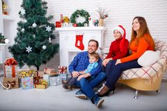 Happy family at Christmas in their house looking away and smiling. Stock Image