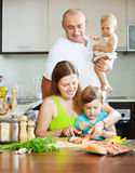 Happy family of four cooking red fish Royalty Free Stock Photos