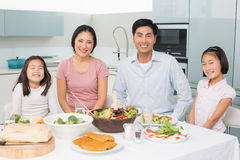 Happy family of four enjoying healthy meal in kitchen. Portrait of a happy family of four enjoying healthy meal in the kitchen at home stock photo
