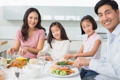 Happy family of four enjoying healthy meal in kitchen. Portrait of a happy family of four enjoying healthy meal in the kitchen at home stock photos
