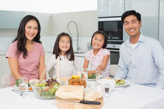 Happy family of four enjoying healthy meal in kitchen. Portrait of a happy family of four enjoying healthy meal in the kitchen at home stock image