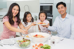 Happy family of four enjoying spaghetti lunch in he kitchen Stock Images