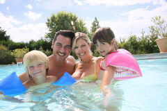 Happy family of four enjoying swimming pool Stock Image