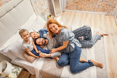 Happy family of four at home Stock Images
