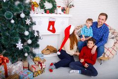 Happy family at Christmas in the house on a background of Christmas trees and fireplace, concept of holidays, new year. Royalty Free Stock Photography