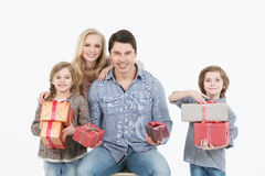 Happy family of four isolated holding gifts Stock Images