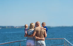 Happy family of four on jetty by the river Stock Image