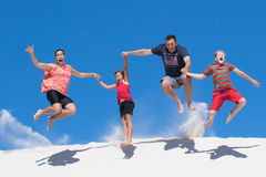 Happy family of four jump from high white sand dune having fun Stock Images